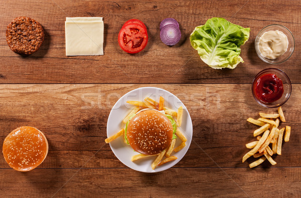 Hamburger ingredients on wooden table with an assembled burger i Stock photo © lightkeeper