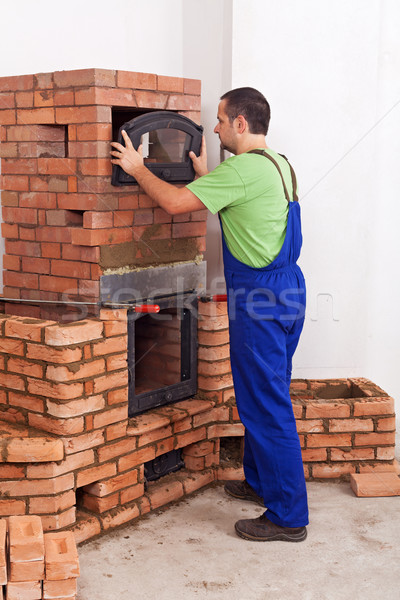 Worker in uniform building a traditional mass stove Stock photo © lightkeeper