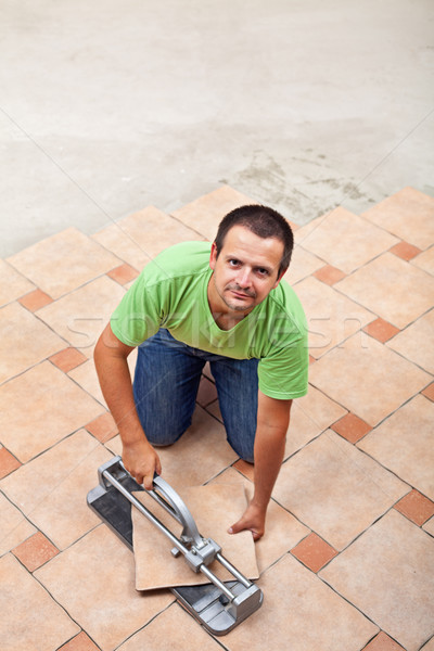 Stock photo: Man laying floor tiles - with copy space
