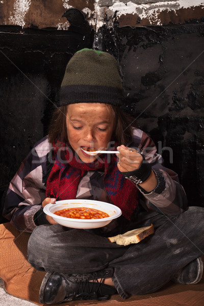 Poor beggar child eating charity food Stock photo © lightkeeper