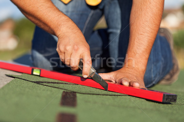 Worker installing bitumen roof shingles Stock photo © lightkeeper