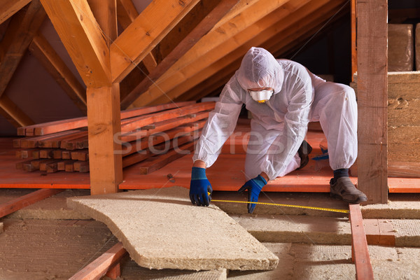 Man laying rockwool panels in the attic of a house Stock photo © lightkeeper