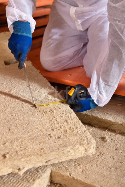 Man cutting rockwool panel to fit in thermal insulation layer Stock photo © lightkeeper