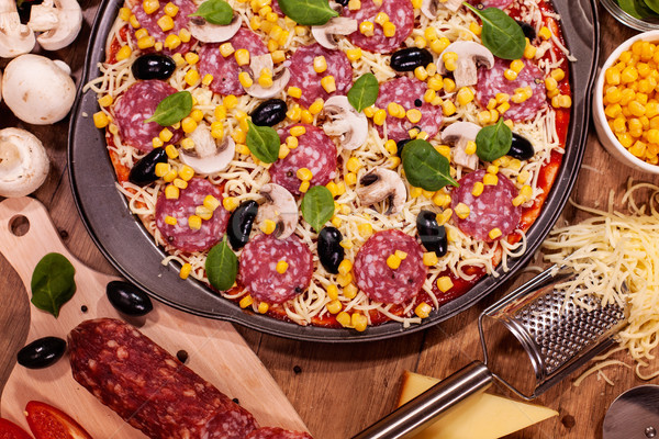 Pizza and ingredients on a table - top view, closeup Stock photo © lightkeeper