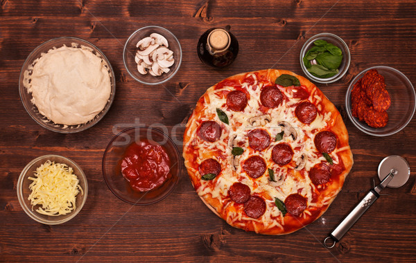 Pizza and ingredients on the table - top view Stock photo © lightkeeper