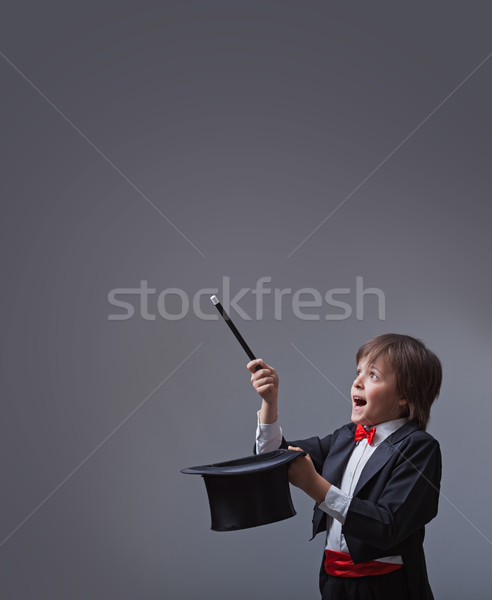 Magician boy performing with magic wand and hard hat Stock photo © lightkeeper