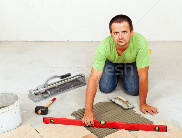 Stock photo: Man laying ceramic floor tiles on concrete floor
