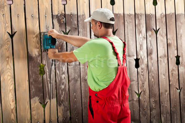 Worker scraping old cracked paint from wooden fence with power t Stock photo © lightkeeper