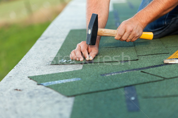 Worker hands installing bitumen roof shingles Stock photo © lightkeeper