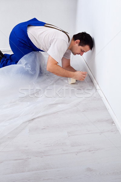 Worker laying protection film before painting Stock photo © lightkeeper