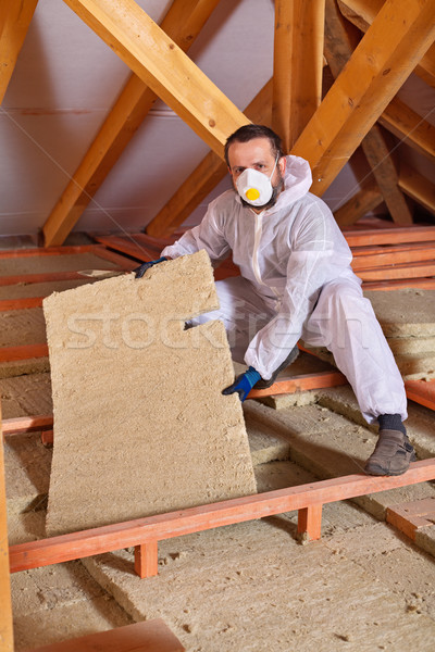 Man installing thermal isnulation with mineral whool panels Stock photo © lightkeeper