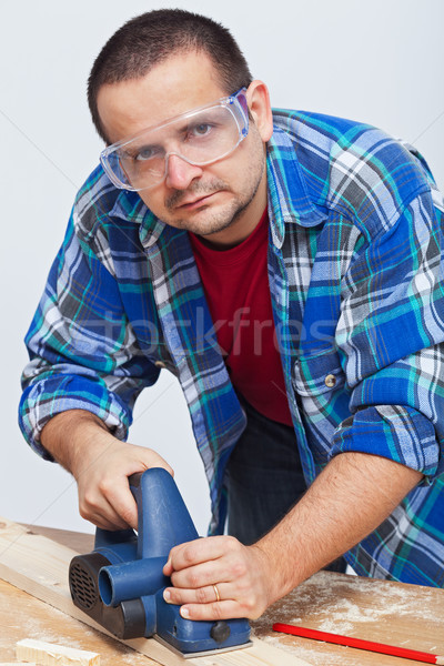 Man working wood with an electric planer Stock photo © lightkeeper