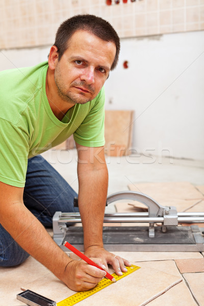 Man marking and cutting ceramic floor tiles Stock photo © lightkeeper
