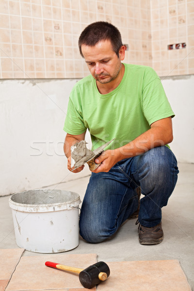 Man installs ceramic floor tiles - preparing the adhesive Stock photo © lightkeeper