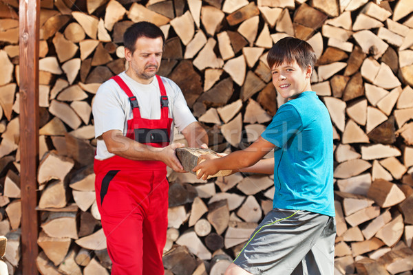 Teenage boy helping father stack the firewood Stock photo © lightkeeper