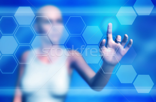 Stock photo: Woman touching virtual buttons on large screen