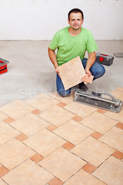 Worker laying floor tiles on concrete surface Stock photo © lightkeeper