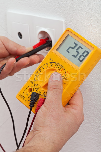 Electrician hands measuring voltage in electrical outlet Stock photo © lightkeeper