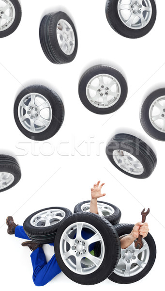 Car mechanic covered with tires Stock photo © lightkeeper