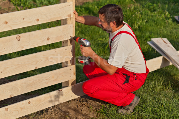 Man building a wooden fence Stock photo © lightkeeper