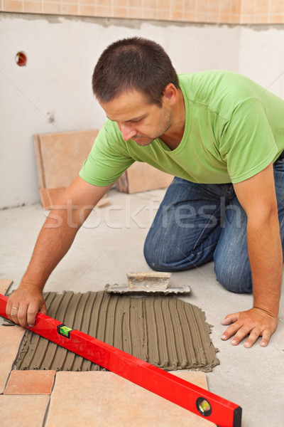 Man laying ceramic floor tiles - checking lines with a level Stock photo © lightkeeper