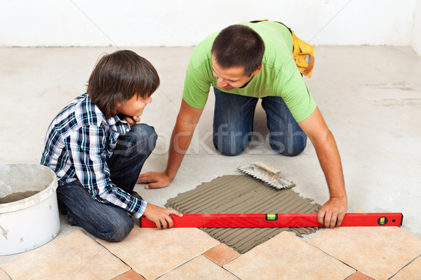 Man and boy laying ceramic floor tiles together Stock photo © lightkeeper