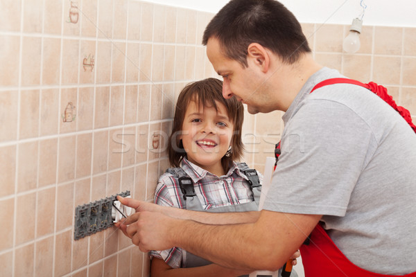 Boy assisting his father installing electical outlets Stock photo © lightkeeper
