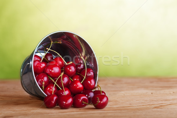 Cherries in a bucket on old wooden table Stock photo © lightkeeper