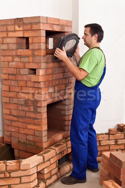 Worker building a masonry heater - trying on an iron and glass d Stock photo © lightkeeper