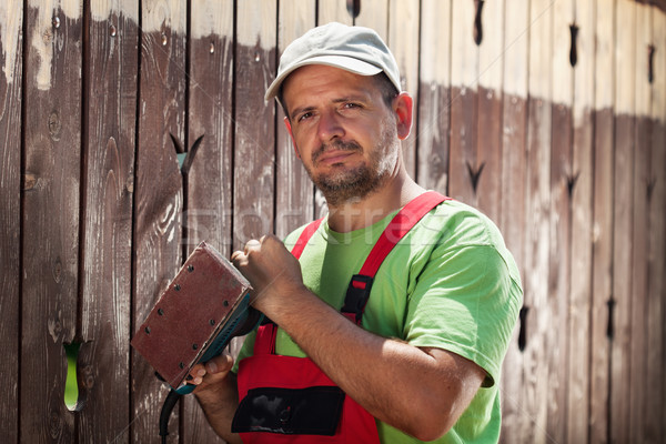 Worker about to scrape away the old paint from a wooden fence Stock photo © lightkeeper