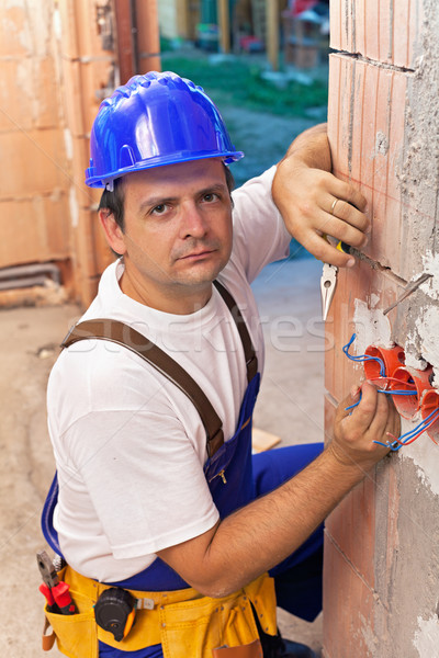 Stock photo: Electrician installing wires in a new building