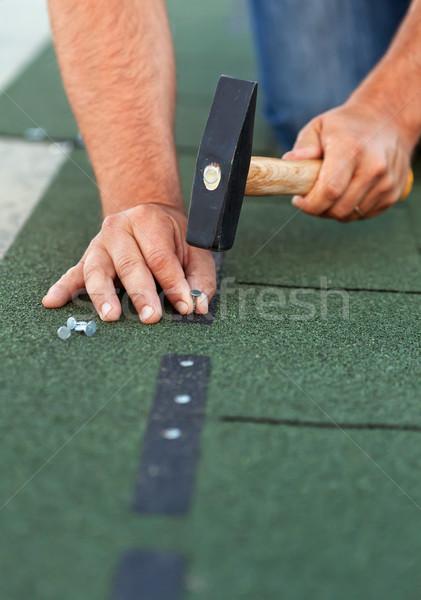 Worker installs bitumen roof shingles - closeup Stock photo © lightkeeper
