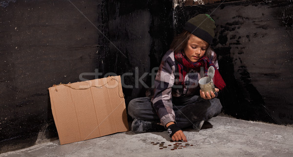 Young beggar boy counting coins - sitting on the ground Stock photo © lightkeeper