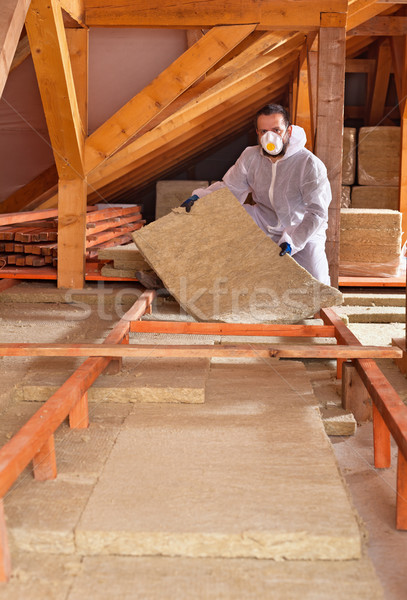 Man places rockwool thermal insulation between wooden scaffoldin Stock photo © lightkeeper