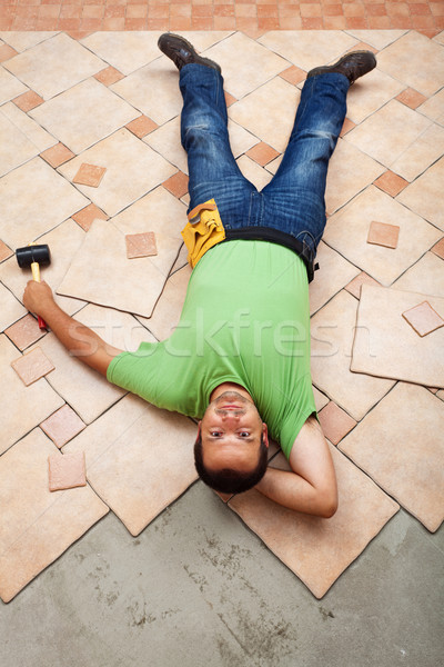 Man resting on ceramic floor tiles he is installing Stock photo © lightkeeper