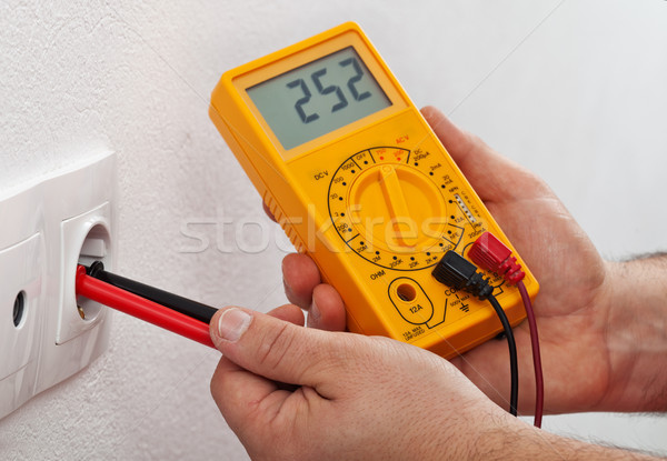 Male hands measuring voltage in electrical wall receptacle Stock photo © lightkeeper