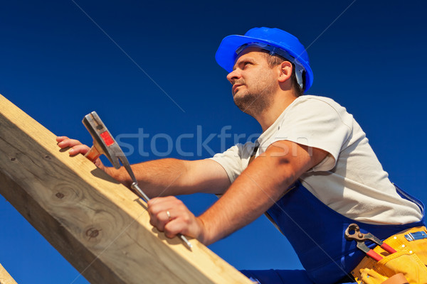 Carpenter on top of roof structure Stock photo © lightkeeper