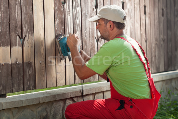 Worker sanding away old paint from a wooden fence Stock photo © lightkeeper