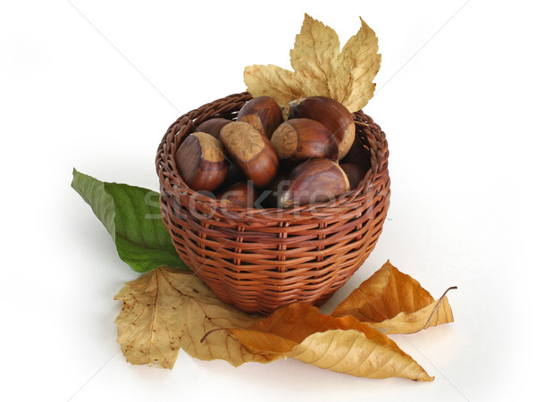 Chestnuts in a basket with autumn leaves Stock photo © lightkeeper