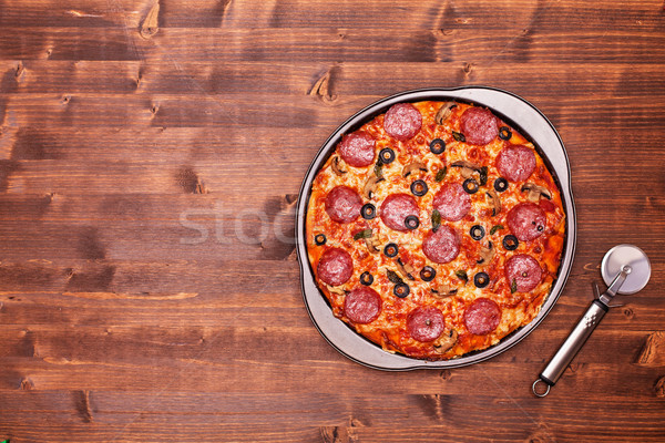 Baked pizza ready to be sliced in the baking pan Stock photo © lightkeeper
