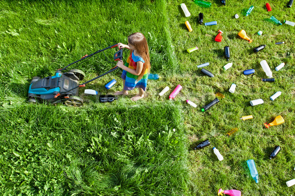 Pollution concept with little girl using plastic spewing lawn mo Stock photo © lightkeeper
