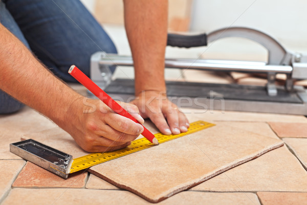 Laying ceramic floor tiles - man hands closeup Stock photo © lightkeeper