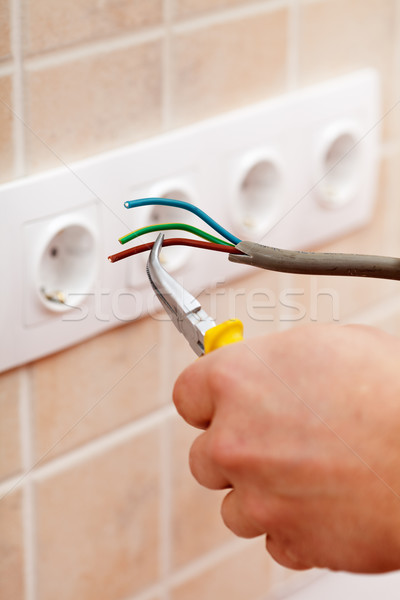 Stock photo: Electrician hands with wires and pliers