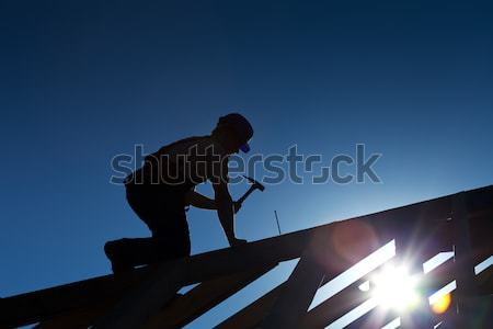 Stock photo: Builder or carpenter working on the roof