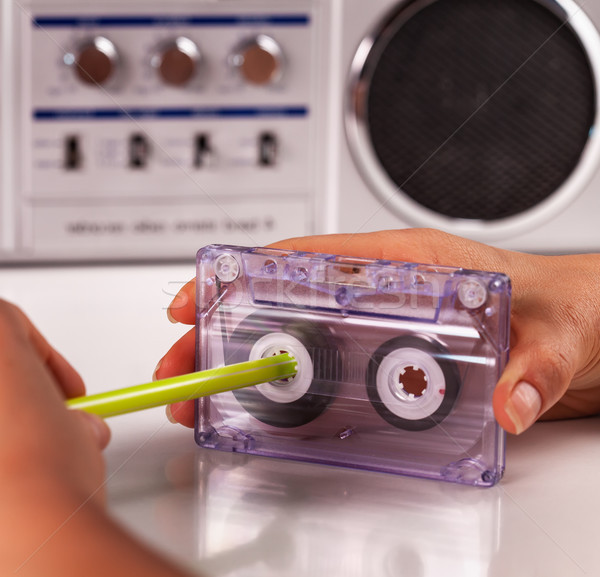 Woman reeling compact audio cassette with a pen Stock photo © lightkeeper