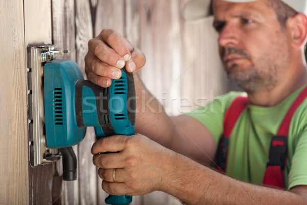 Worker scraping vertical wooden surface with vibrating sander -  Stock photo © lightkeeper