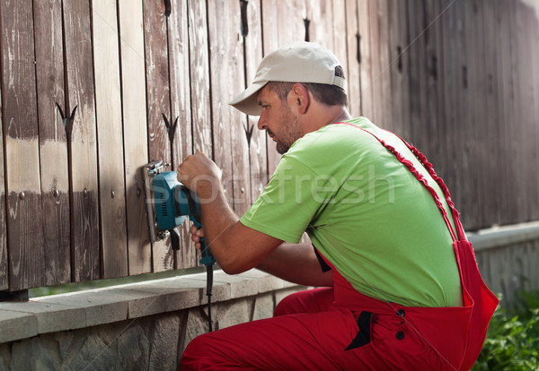 Worker removing old paint from fence Stock photo © lightkeeper
