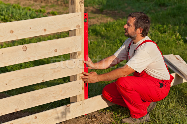 Man building wooden fence Stock photo © lightkeeper