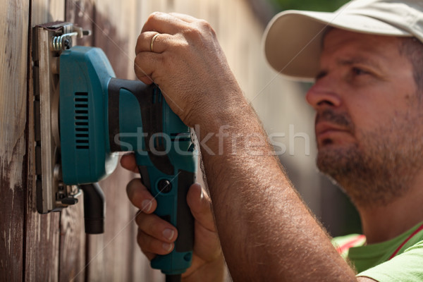 Worker using a vibrating sander on a wooden fence Stock photo © lightkeeper