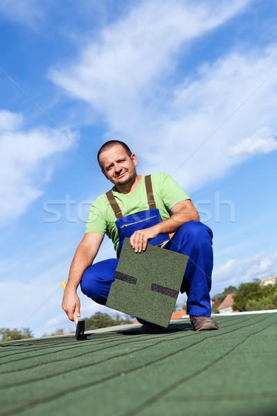 Worker installs bitumen roof shingles Stock photo © lightkeeper